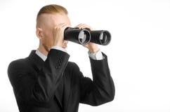 Assunto do negócio e da busca: O homem no terno preto que guarda os binóculos pretos disponivéis no branco isolou o fundo no estú Fotos de Stock Royalty Free