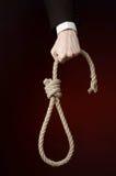 Assunto do suicídio e do negócio: Mão de um homem de negócios em um revestimento preto que guarda um laço da corda para pendurar  foto de stock