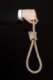 Assunto do suicídio e do negócio: Mão de um homem de negócios em um revestimento preto que mantém um laço da corda para pendurar  fotos de stock royalty free