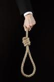 Assunto do suicídio e do negócio: Mão de um homem de negócios em um revestimento preto que mantém um laço da corda para pendurar  fotografia de stock royalty free