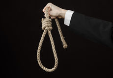 Assunto do suicídio e do negócio: Mão de um homem de negócios em um revestimento preto que mantém um laço da corda para pendurar  fotos de stock