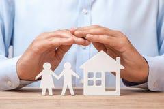 Assurance d'une jeunes famille et maison L'homme dans la chemise couvre ses mains de couples des hommes et femme et maison Photographie stock