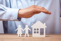 Assurance d'une jeunes famille et maison L'homme dans la chemise couvre ses mains de couples de deux hommes et femme et maison Image libre de droits