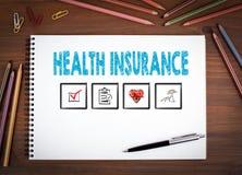 Assurance médicale maladie Carnets, stylo et crayons colorés sur une table en bois Image libre de droits