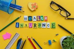 Assurance médicale maladie - mot des lettres découpées à l'agent d'assurance de lieu de travail de bureau Image libre de droits