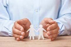 Assurance médicale ou de voyage L'homme couvre sa famille d'homme et de femme images stock
