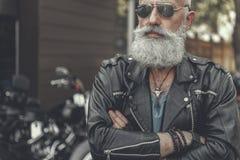 Assured aged man locating near motorbike Stock Photos