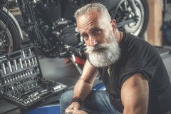 Assured aged man in workshop Royalty Free Stock Photos