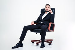 Assured confident business man with beard sitting in office chair. Full lenght of assured confident young business man with beard in black suit sitting in office royalty free stock images