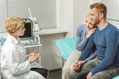 Assured doctor giving consultation to couple stock photos