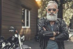 Assured elder man locating near motorcycle Stock Images