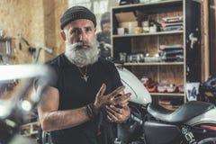 Assured old man in garage Royalty Free Stock Photo