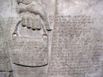 Assyrian relief 865-860 BC showing cuniform script. Assyrian relief 865-860 BC, showing cuniform script, of a royal helper carrying a bucket Royalty Free Stock Photography