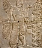 Assyrian wall relief of a winged genius with cuneiform. Ancient carving panel from the Middle East history. Remains of the culture of ancient Assyrian and stock photo
