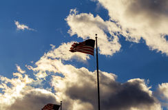 Asta de bandera de la bandera americana que agita en el viento contra las nubes, cielo azul Fotografía de archivo libre de regalías