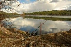 Asta di pesca disposto sul vicino a terra un lago immagine stock
