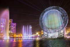 Astana Kasakhstan - Augusti 28, 2016: Musikalisk solspringbrunnshow i Ishim flodinvallning med byggnader på bakgrund arkivbild