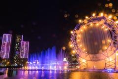 Astana Kasakhstan - Augusti 28, 2016: Musikalisk solspringbrunnshow i Ishim flodinvallning med byggnader på bakgrund fotografering för bildbyråer