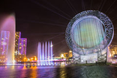 Astana, Kazakhstan - August 28, 2016: Musical sun fountain show in Ishim river embankment with buildings on background Stock Photography