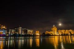 astana kazakhstan Ishim flodinvallning i månenatten med byggnader och reflexion i vattnet arkivfoto