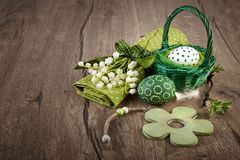 Еaster eggs, lily of the valley and spring decorations on wood. Easter still life on wood in green and white. Easter eggs, lily of the valley flowers and wooden Stock Photography