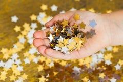 Asteriscos que brillan la Navidad en las manos de un niño y dispersadas en un fondo de oro Fotografía de archivo libre de regalías