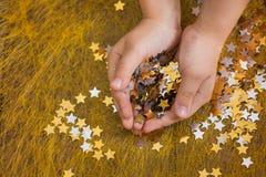 Asteriscos que brillan la Navidad en las manos de un niño y dispersadas en un fondo de oro Fotografía de archivo