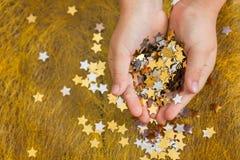 Asteriscos que brillan la Navidad en las manos de un niño y dispersadas en un fondo de oro Foto de archivo