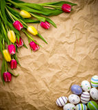 Astern egg, tulips on brown crumpled wrapping paper Royalty Free Stock Photography