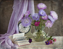 Asters. Bouquet of blue asters, clock and book on a table Royalty Free Stock Photo