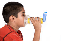 Asthma. Close up image of a cute little boy using inhaler for asthma. White background royalty free stock images