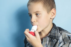 Asthma boy with is inhalator over blue background Stock Images