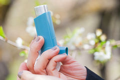 Asthma inhaler close up outdoor during springtime. Close up picture of an asthma inhaler in a woman`s hands outdoor during springtime Stock Photography