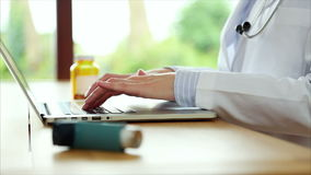 Asthma inhaler with doctor typing on laptop in medical clinic. Rack focus of asthma inhaler with female doctor's hands using laptop. Professional is typing on stock video