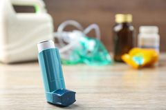 Asthma inhaler, nebuliser and medicines. On wooden table Royalty Free Stock Image