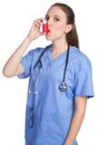 Asthma Inhaler Nurse. Pretty nurse using asthma inhaler Stock Photo