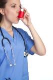 Asthma Inhaler Nurse. Pretty nurse using asthma inhaler Stock Photos