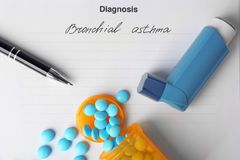 Asthma inhaler, pills and pen on diagnosis. Form Stock Images