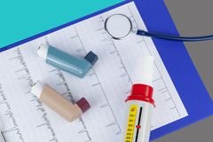 Asthma inhalers and a peak flow meter on a medical clipboard. Stethoscope with two asthma inhalers and a peak flow meter on a medical clipboard stock photo