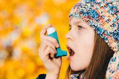 Asthma patient girl inhaling medication for treating shortness o. F breath and wheezing in a park. Chronic disease control, allergy induced asthma remedy and royalty free stock photos
