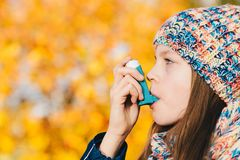 Asthma patient girl inhaling medication for treating shortness o. F breath and wheezing in a park. Chronic disease control, allergy induced asthma remedy and Royalty Free Stock Photo