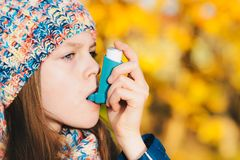 Asthma patient girl inhaling medication for treating shortness o. F breath and wheezing in a park. Chronic disease control, allergy induced asthma remedy and Stock Photo