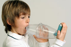 Asthma - plastic spacer. Child using plastic spacer for inhaling asthma medicine royalty free stock photo