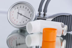 Asthma spray and blood pressure gauge Stock Photography