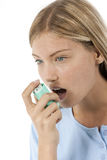 Asthma Sufferer. Young woman using asthma inhaler Royalty Free Stock Photo
