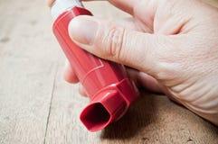 Asthmaaerosol in der Hand auf Holztisch Lizenzfreie Stockbilder