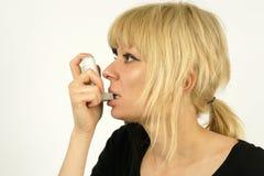 Asthmatic. An asthma sufferer using an inhaler stock image