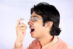 Asthmatic. A portrait of an asthmatic young Indian guy using a medicinal inhaler stock photos