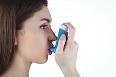 Asthmatic brunette using her inhaler. On white background stock image