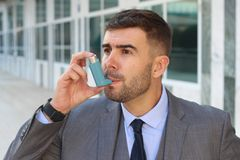 Asthmatic businessman using an inhaler at work.  royalty free stock photography